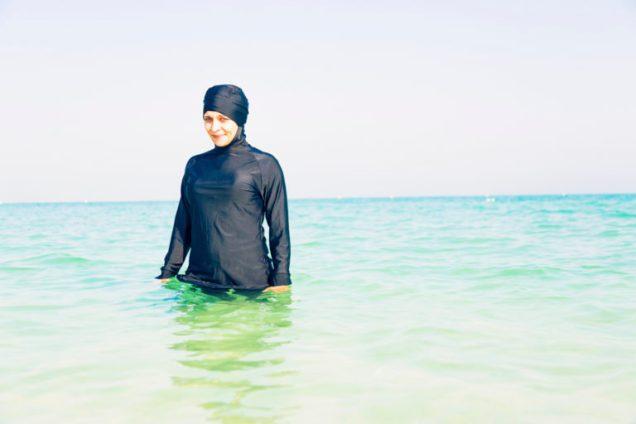 young woman in burkini swimming in the sea